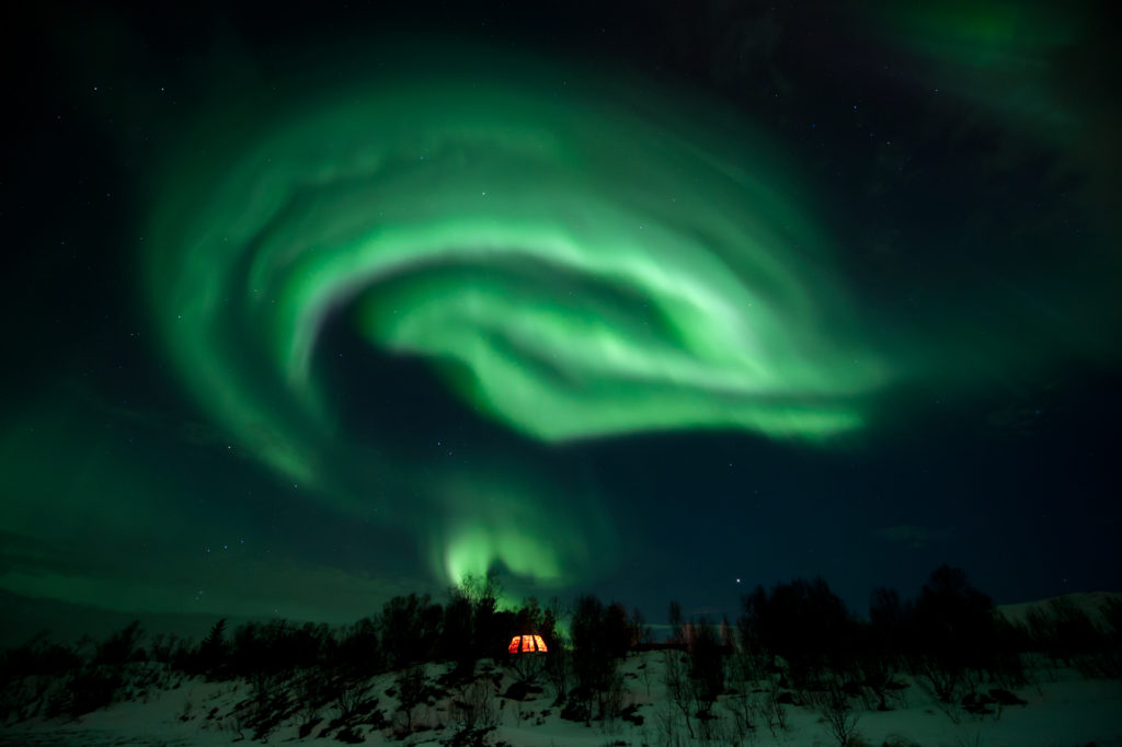 The Northern Lights shining brightly above the Tromsø Wilderness Centre.